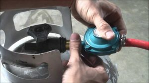 hands putting on a gas cylinder measuring attachment