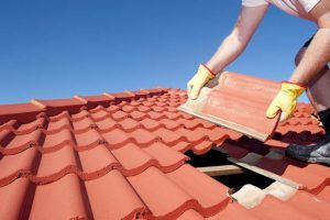 man putting a roof tile on a roof